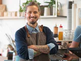 Smiling male barista with arms folded